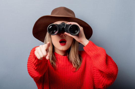 woman in red sweater and hat with binocular