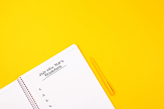 2020 PLAN. White notebook on a yellow background, yellow pen, goals for the year.