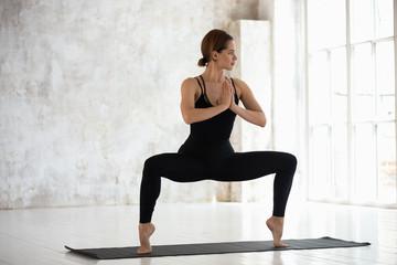 Beautiful woman standing in Goddess pose, Sumo Squat, yoga exercise