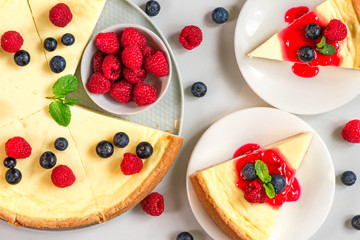 sweet cake or cheesecake with two slices of cake with fresh raspberries, blueberries, jam and mint