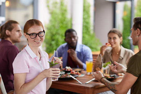 Portrait of red haired young woman smiling at camera and holding cocktail while enjoying lunch together with friends in cafe, copy space