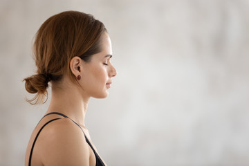 Beautiful woman with closed eyes practicing yoga, meditating, profile view