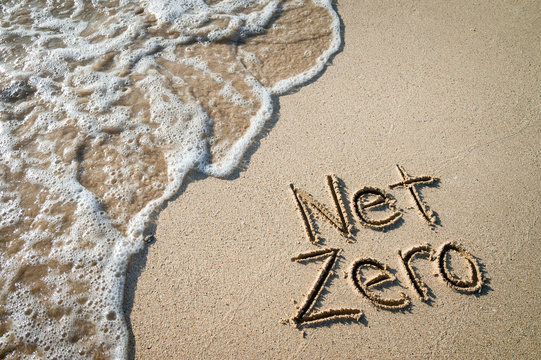 Net Zero message for energy consumption handwritten on smooth sand beach with oncoming wave