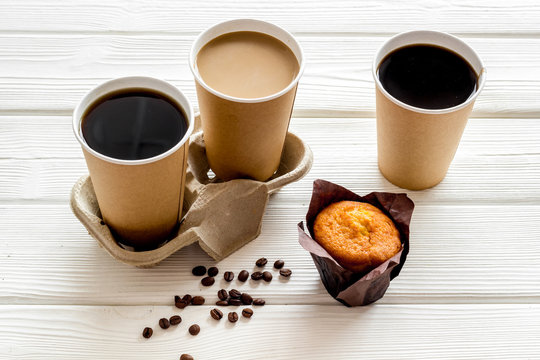 Coffee to take away in paper cups, beans with muffin on white wooden table background