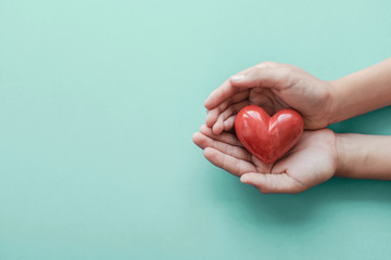 hands holding red heart on blue background, health care, love, organ donation, wellbeing family insurance and CSR concept, world heart day, world health day, hope, gratitude concept