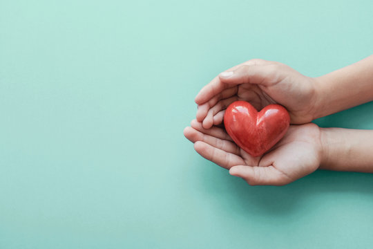 hands holding red heart, health care, love, organ donation, wellbeing family insurance and CSR concept, world heart day, world health day, hope, gratitude, covid-19, coronavirus relief concept