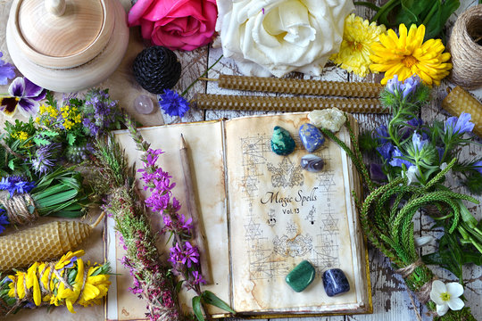Witch spell book, calendula, rose flowers, reiki crystals and candles on wooden table.