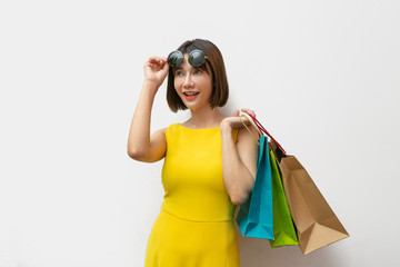 Portrait of beautiful girl wearing dress and sunglasses holding shopping bags.