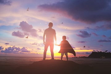 Super Son holding hand of fatheroutdoors on background sunset. Father holiday