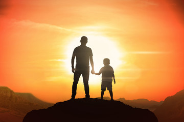 Father and son holding hand in hand at the sunset time.
