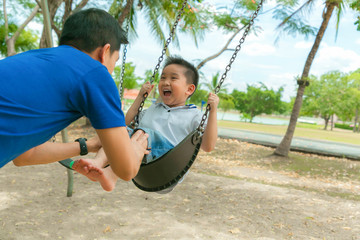Father and son having funny on swing in playground.