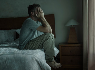 Attractive depressed and sad man at home sitting on bed crying desperate suffering depression problem