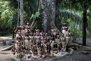 Indigenous women from the Shanenawa tribe pose for a photo near a Sumauma tree during a festival in the indigenous village of Morada Nova near Feijo