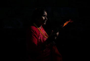 Light illuminates a woman as she offers prayers holding a lamp at the premises of Pashupatinath Temple during the Teej festival in Kathmandu