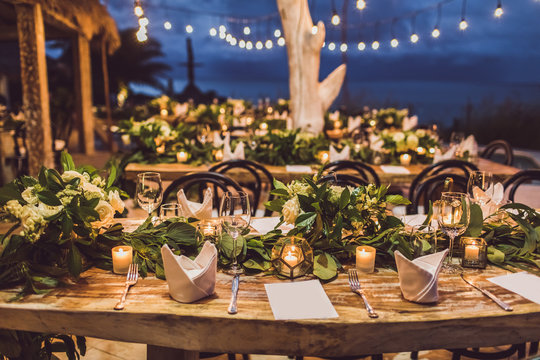 Table setting at night wedding ceremony. Decoration with fresh flowers, candles, light bulbs, garlands. Vintage style.