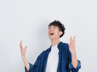 Portrait of a handsome Chinese young man in blue shirt shouting with two arms open, smiling and happy expression, isolated on white background.