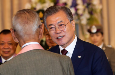 South Korean President Moon Jae-in talks to Korean War veterans after a news conference at the government house in Bangkok