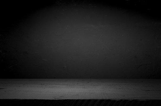 cement floor in dark room with spot light. black background.