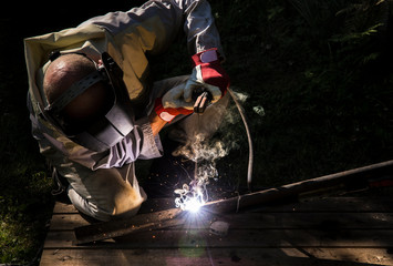 Man welding metal construction outdoors, wearing protective mask and gloves, sparks fly.