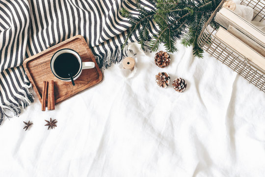 Christmas styled composition. Cup of coffee, plaid, old books in golden basket, pine cones, fir branches on white table, linen background. Flat lay, top view. Winter holiday lifestyle concept, web