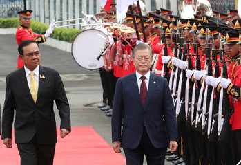 South Korean President Moon Jae-in, right, escorted by Thailand's Prime Minister Prayuth Chan-ocha, left reviews an honor guard during a welcoming ceremony at the government house in Bangkok, Thailand