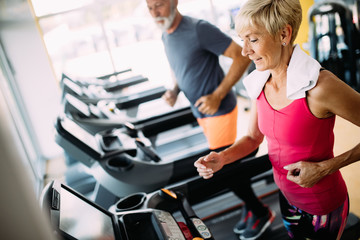 Happy senior people running together on treadmills in gym.