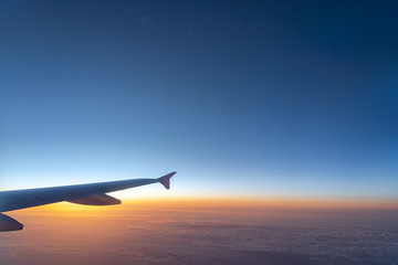 Up in the air, view of aircraft wing silhouette with dark blue sky horizon and cloud background in sun rise time, viewed from airplane window
