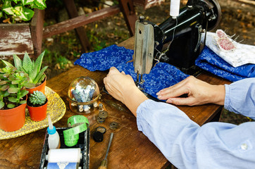 Woman works on a vintage sewing machine – old sewing work station with accessories - cosy interior with green plants and antiquities