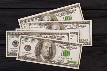 Four hundred American dollars on dark background. USA dollars banknotes on black wooden surface.