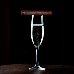 Picture of tall glass of champagne and Cuban cigar on top of it on wooden   table with black background