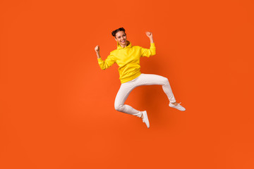Full size photo of cheerful millennial jumping with raised hands arms wearing pants trousers isolated over orange background