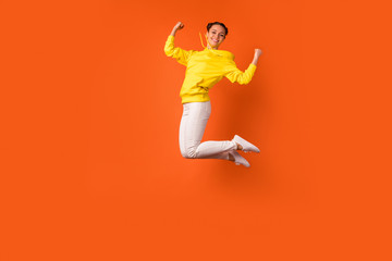 Full body photo of lovely teen raising fists smiling isolated over orange background Wall mural