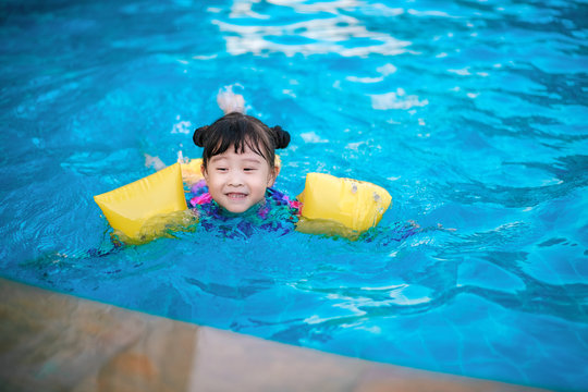 asian little girl in swimming pool