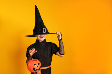 Halloween celebration. Little girl in a witch costume holds a pumpkin jack bucket on a yellow background. The child hid his face under the hat. Wall mural