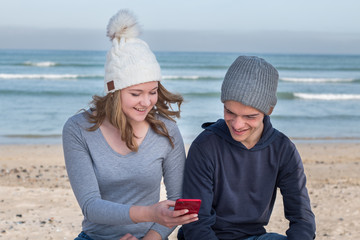 Happy male and female models wearing knitted beanies with Bluetooth speakers inside, listening to music together with mobile smart phone. Looking at mobile device.