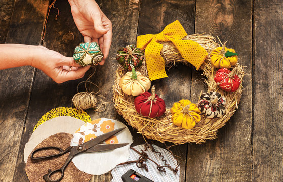 Female hands sew a textile pumpkin to decorate an autumn straw wreath on a wooden background. DIY