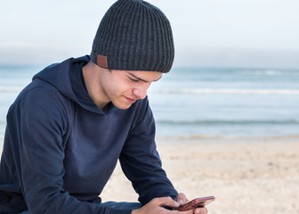 Male model wearing dark grey knitted beanie with Bluetooth speakers inside, listening to music with mobile smart phone outdoors. Looking at mobile device.