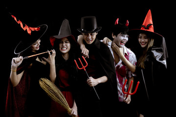 Group young Asian in costume Halloween party on black background.