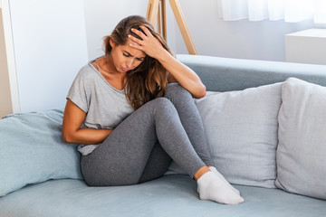 View of young woman suffering from stomachache on sofa at home. Woman sitting on bed and having stomach ache. Young woman suffering from abdominal pain while sitting on sofa at home