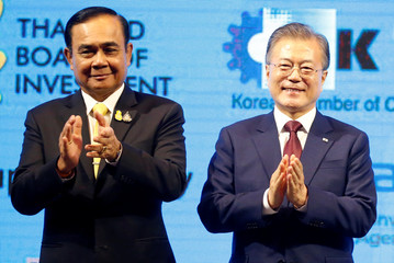 Thailand's Prime Minister Prayuth Chan-ocha and South Korean President Moon Jae-in clap as they attend Thailand-Korea Business forum in Bangkok