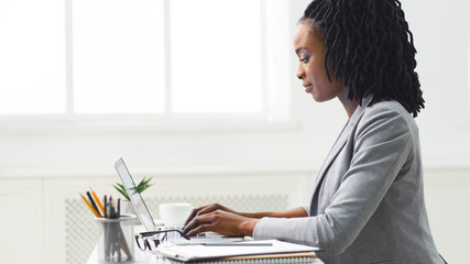 Young Afro Woman Working On Laptop Computer At Workplace