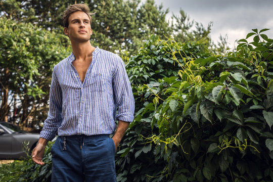 Young handsome man in casual clothes  pose in summer garden.