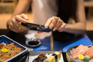 woman photographing food by smartphone
