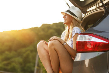 Casual look female on travel . She sitting on car trunk and relaxing after long journey.