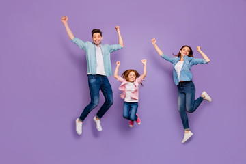 Full length photo of three cheerful jumping high family members wear casual clothes isolated purple...