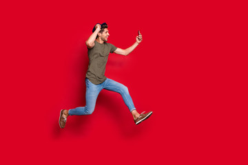 Full size profile photo of cool guy jumping high making selfies wear casual outfit isolated on red background