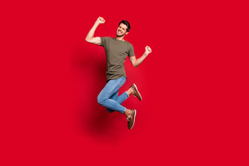 Full length photo of amazing guy jumping high ecstatic win wear casual outfit isolated on red...
