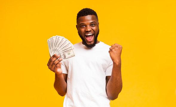 Handsome black guy holding fan of dollars celebrating success