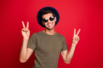 Photo of traveler guy showing hands v-sign wear vintage hat sun specs and grey t-shirt isolated on red background