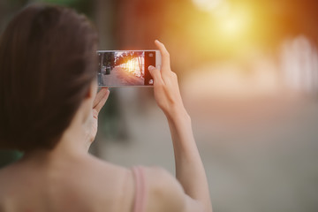 Woman taking a sunset photo on the beach at PATTAYA in THAILAND with her smart phone.